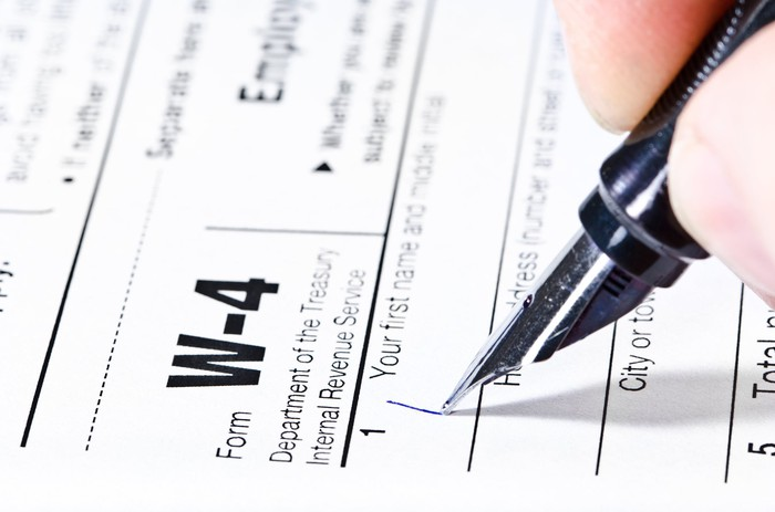 A hand holds a pen and begins filling out Form W-4