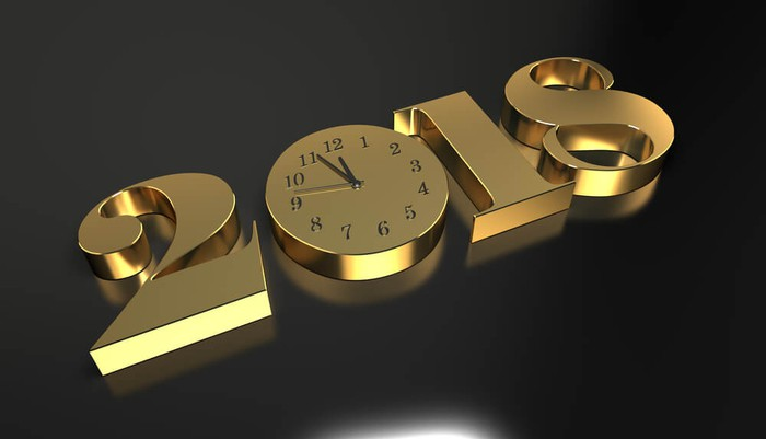 The year 2018 in gold, block-like numbers using a round clock as the 0.