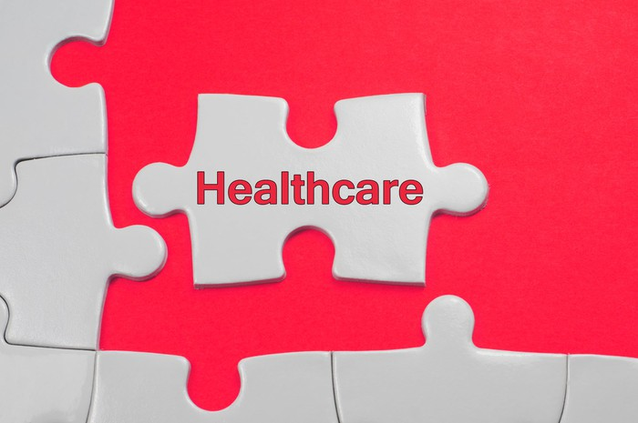 Puzzle pieces being arranged. One piece has the word healthcare written on it.
