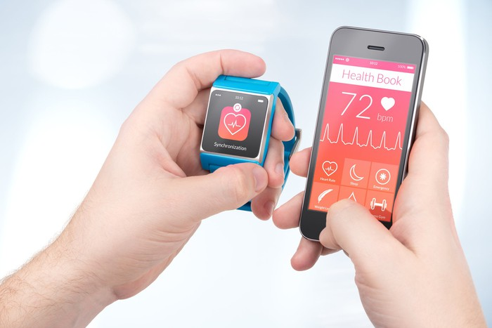 A person compares their heart beat on a watch to a display on a smartphone.