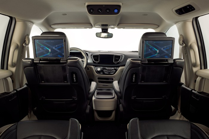 The interior of Waymo's Pacifica minivan, viewed from the back seat, showing touchscreens positioned for the passengers' use.