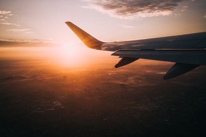 Image from inside a commercial airplane of a sunset and plane wing