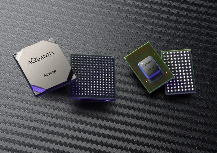 Two pairs of semiconductor chipsets against a textured dark grey background.