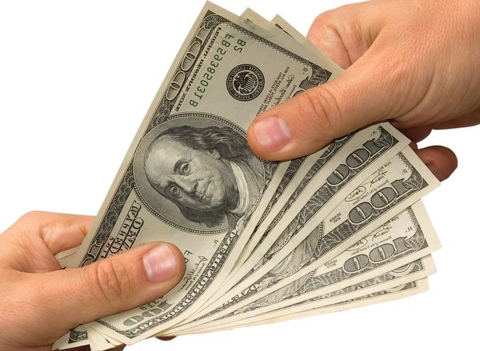 Handing over several hundred dollar bills.