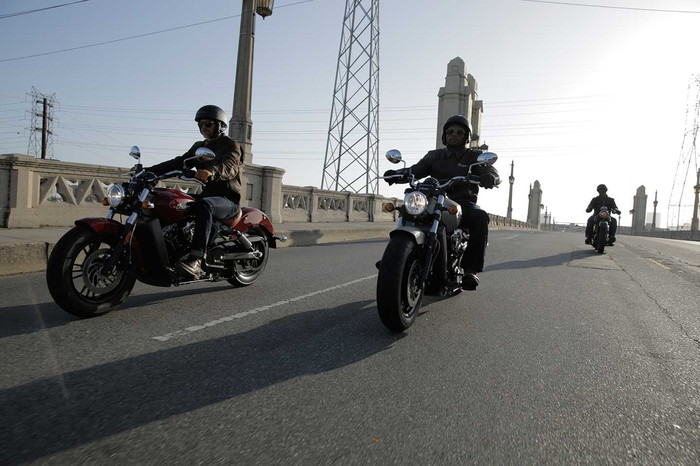 Three motorcycle riders on a bridge on a sunny clear day.