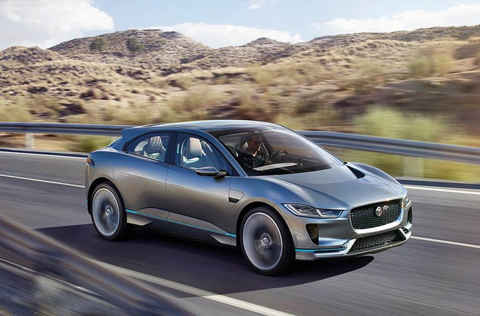 The Jaguar I-PACE in silver driving down a desert highway.