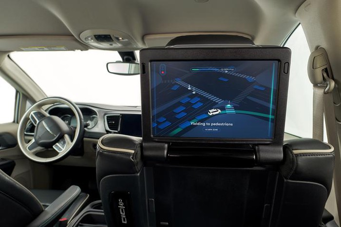 A rear-facing display screen in a self-driving car shows a map route.