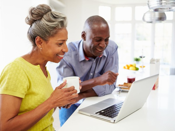 mature man and woman sitting in kitchen looking at laptop computer and smiling -- couple POC