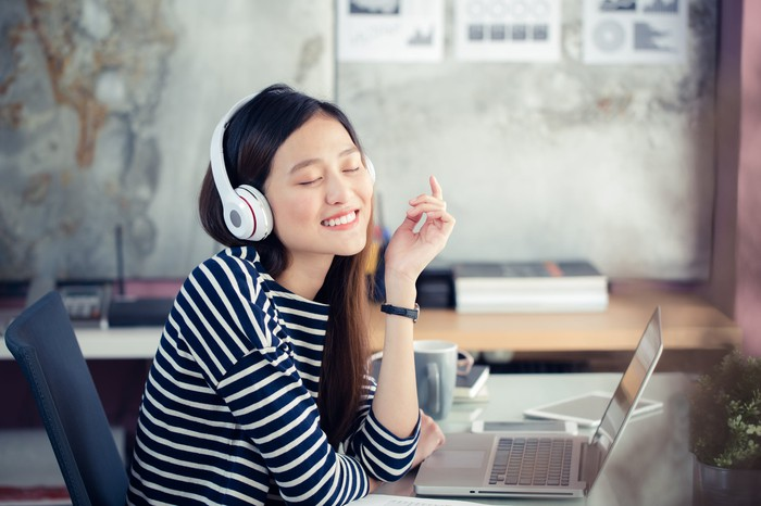 A woman listens to music on her laptop.