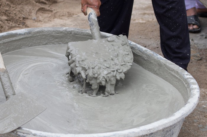 A person mixing cement with a shovel.