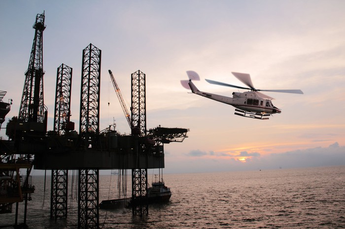 A helicopter taking off from an offshore oil rig.