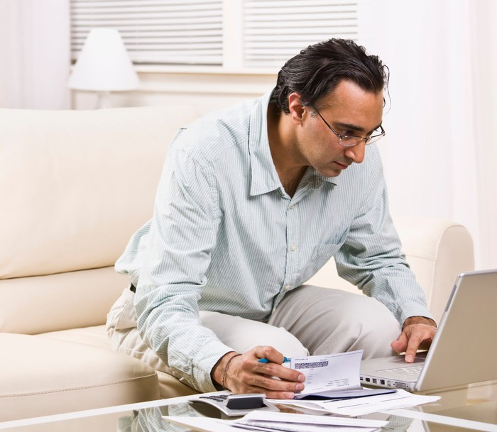 Man holding checkbook and looking at computer screen.