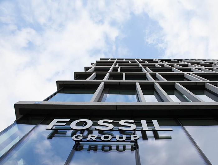 Fossil Group headquarters sign on a tall glass building from below