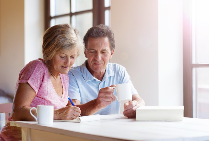 An older couple sits side by side near a window with light coming in. The man holds a coffee cup and looks on while the woman writes on a pad of paper.