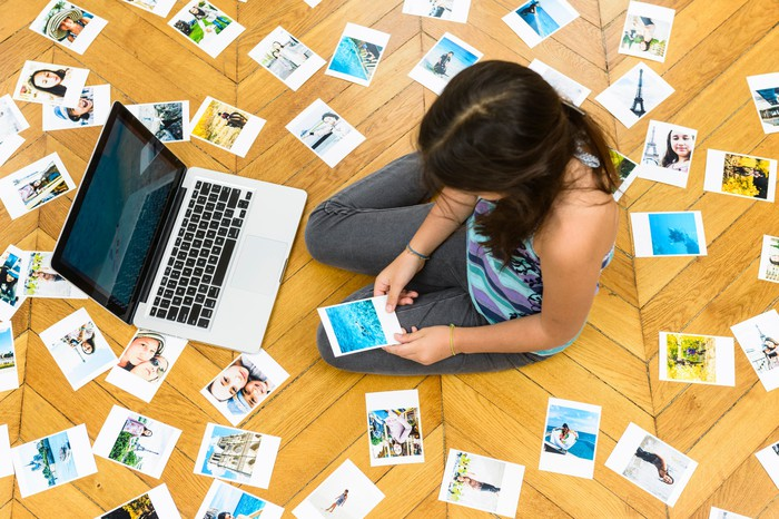 Woman sitting on a floor reviewing photos.