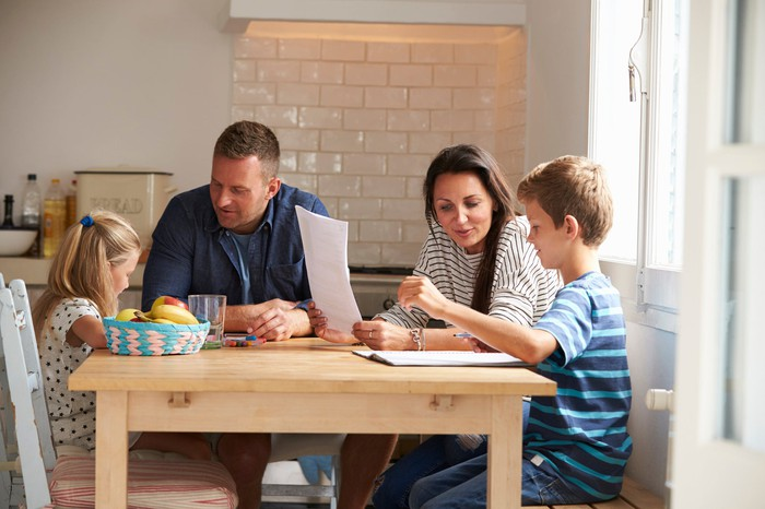 Two adults and two children sitting and talking at a kitchen table.