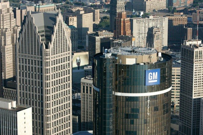 "An aerial photo of the top of the GM Renaissance Center, a cylindrical skyscraper in downtown Detroit, showing the large ""GM"" logo at the top of the building."