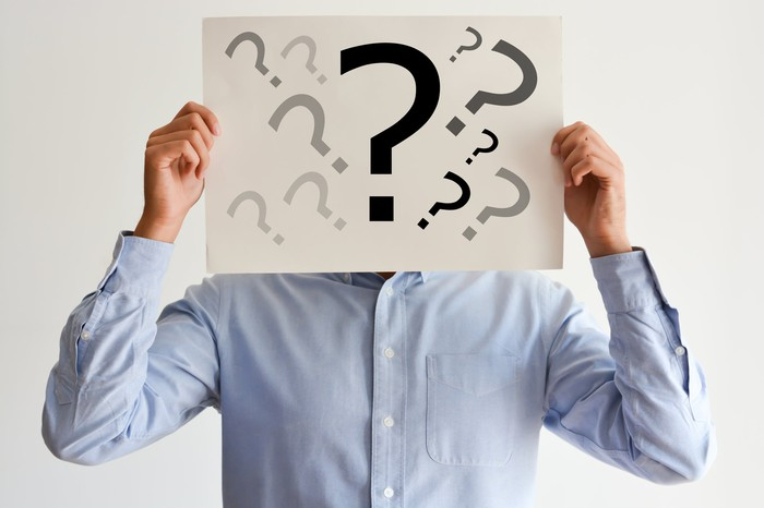 A man holding a sign in front of his head with multiple question marks.
