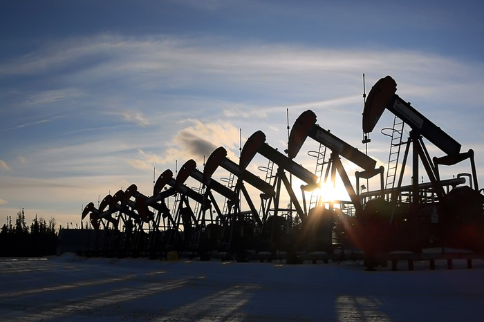 A long row of pumpjacks under the setting sun with snow in the foreground.