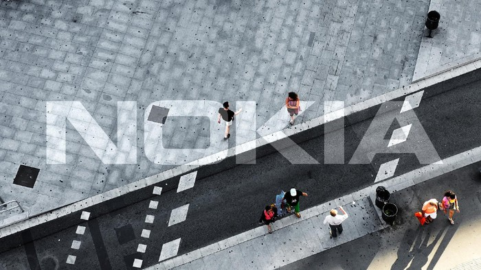 Nokia's logo overlaid on the backdrop of a sparsely populated city sidewalk.