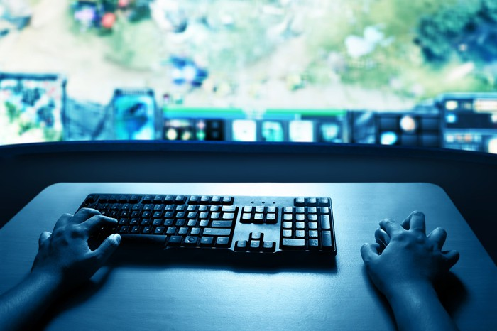 Hands on computer keyboard and mouse with PC monitor displaying a game in the background.