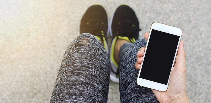 A woman in running pants holds a smartphone in her hands.