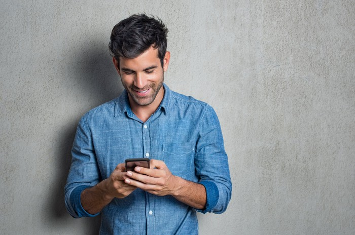 A man looks at his smartphone and smiles.