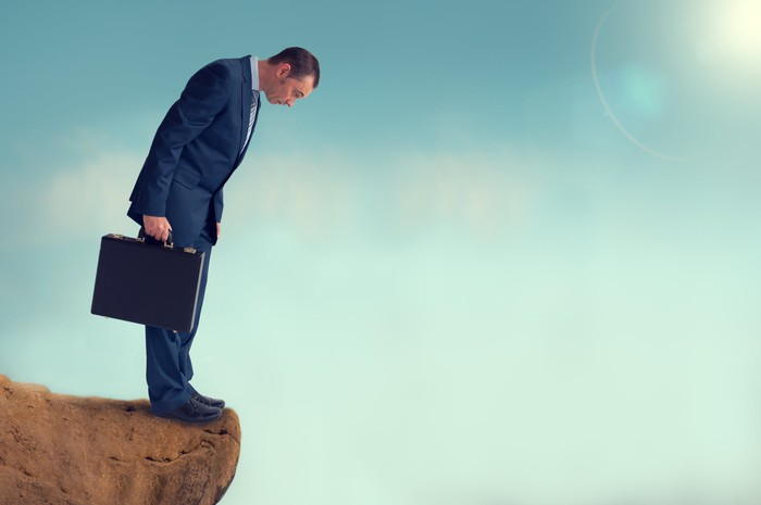 Man wearing a suit and holding a briefcase, looking over a cliff.