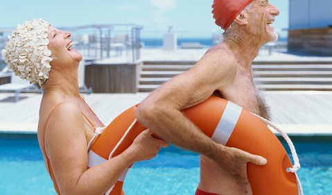 Retiree seniors couple swiming with life ring