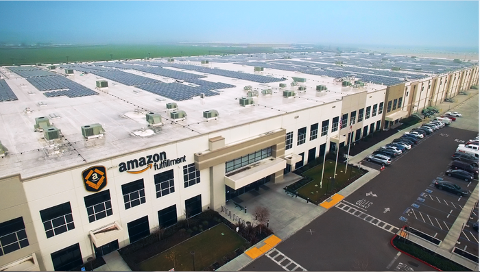 A huge Amazon fulfillment center complex showing bay doors for trucks, with a blue sky in background.