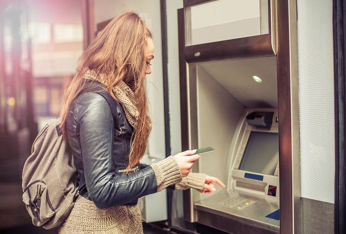 A woman prepares to enter her card into an ATM.