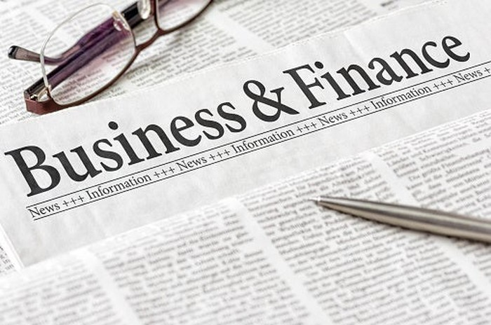 Close-up of the business and finance section of a newspaper, with a pen and a pair of glasses.