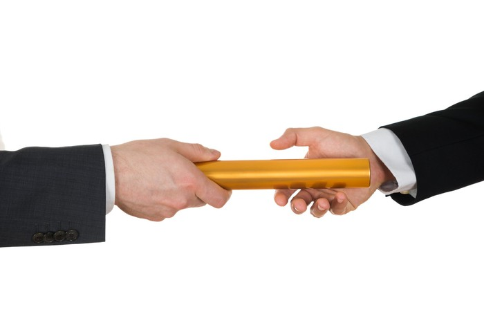 One hand passes a golden baton to another suit-dressed hand.