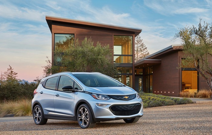 A light blue Chevrolet Bolt EV, a small electric hatchback, in front of an upscale house.