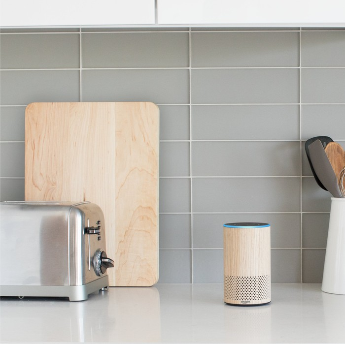 An Amazon Echo smart speaker on a kitchen counter near a toaster and cutting board.