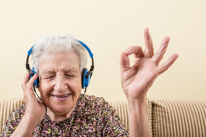 An elderly woman wearing headphones smiles as she makes the OK sign with her fingers.