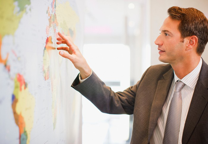 Man in suit pointing at world map.