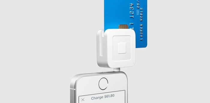 Square's card reader attached to an iPhone capturing a credit card.
