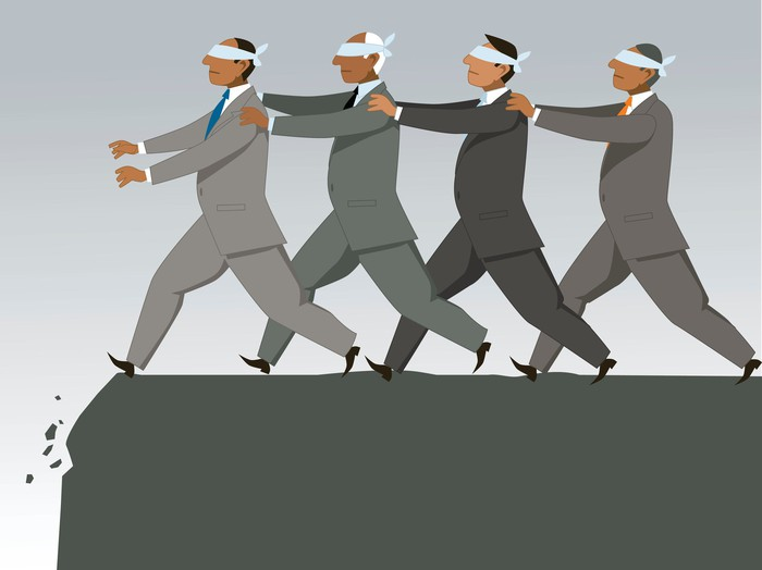 Group of blindfolded businessmen following each other in single file to the edge of a cliff.