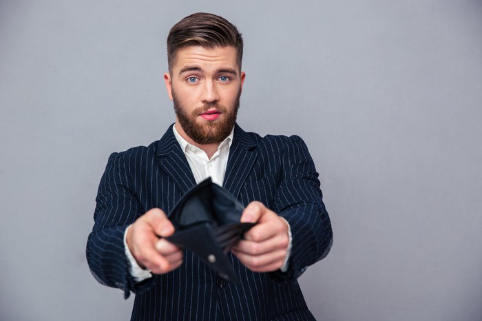 Un homme d'affaires bien habillé tenant son portefeuille vide ouvert.