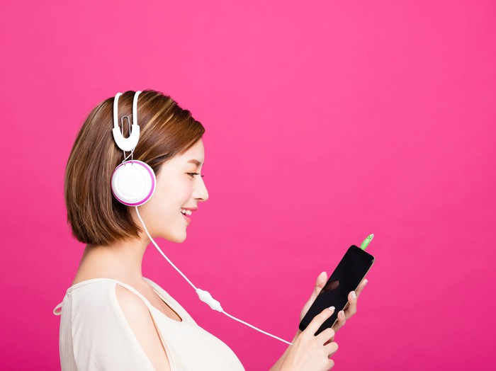A woman listens to music on her smartphone.