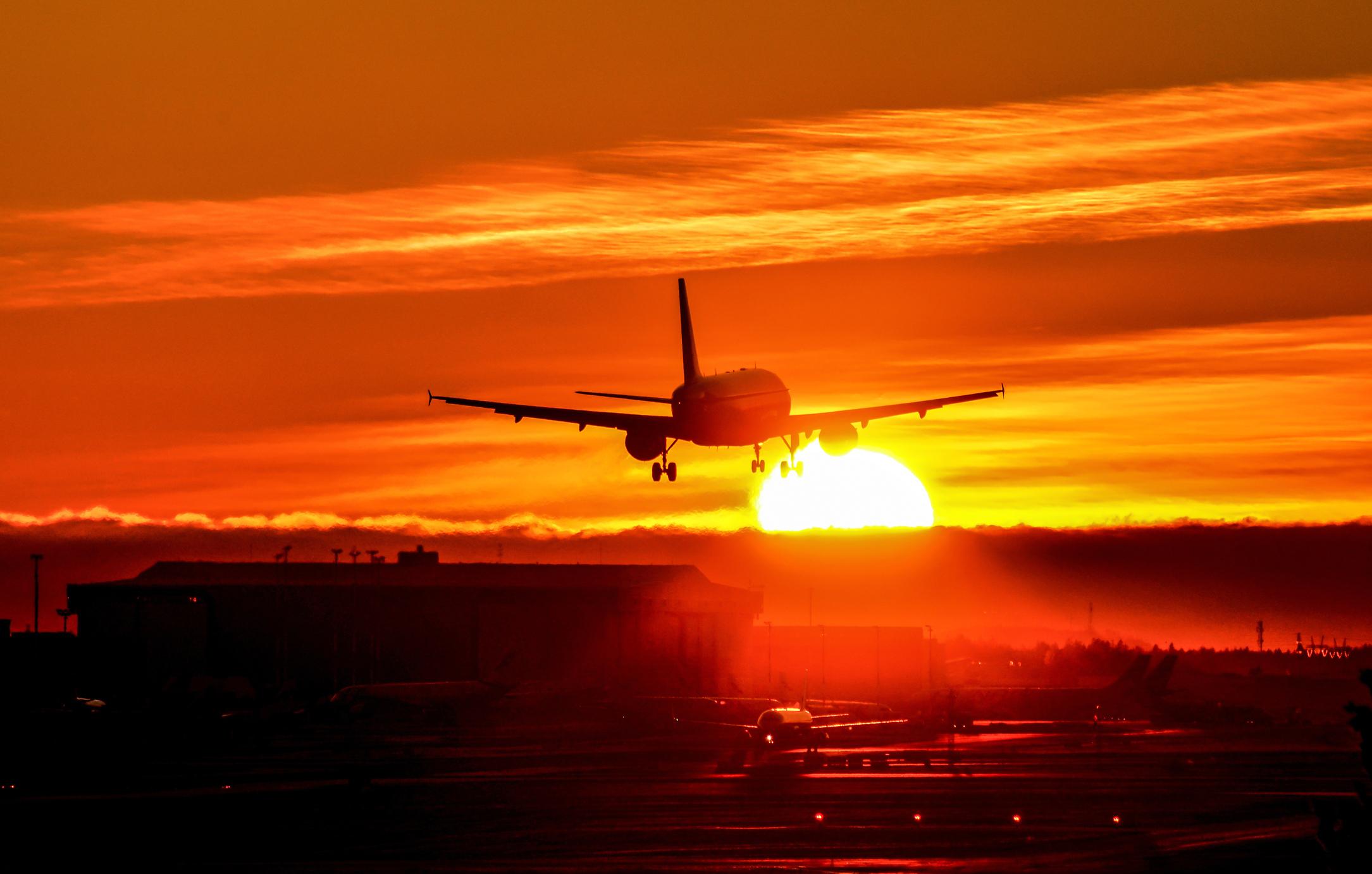 A plane landing as the sun sets
