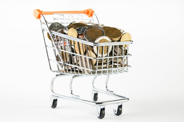 Miniature shopping cart filled with coins