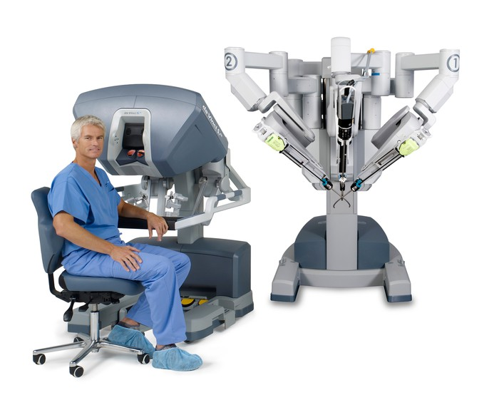 A surgeon sitting in front of a surgeon console as part of a da Vinci system.