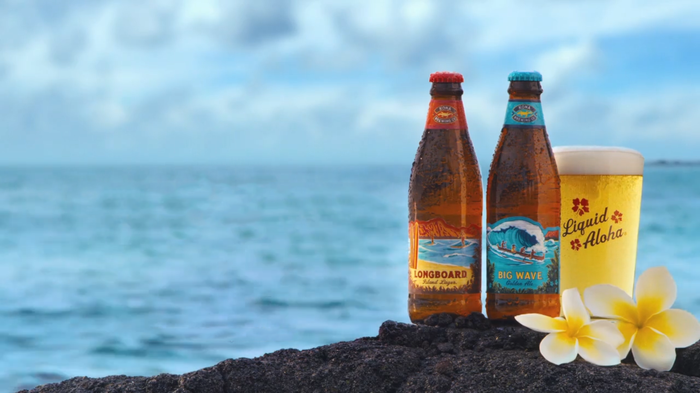 Two bottles of Kona Brewing beer with ocean in the background.