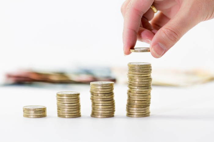 Hand building successively taller stacks of coins, dividend concept