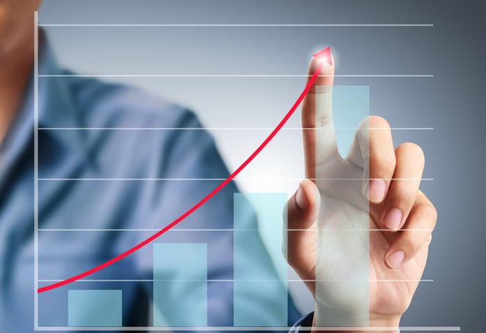 A man touching an arrow going up over a bar graph.