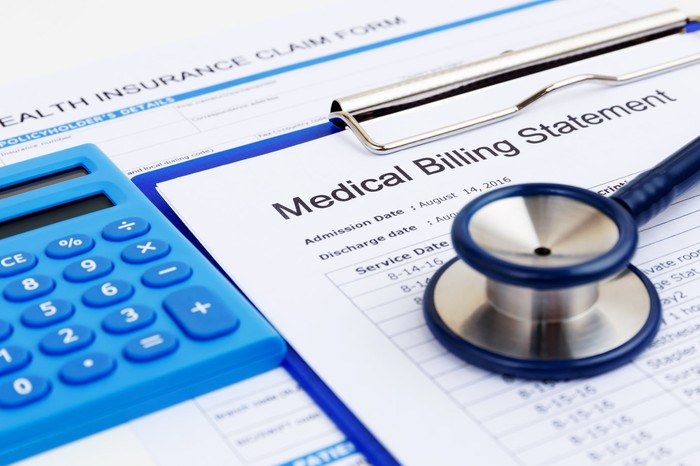 A Medical Billing Statement on a blue clipboard, next to a blue calculator, with a blue stethoscope sitting on top of it.