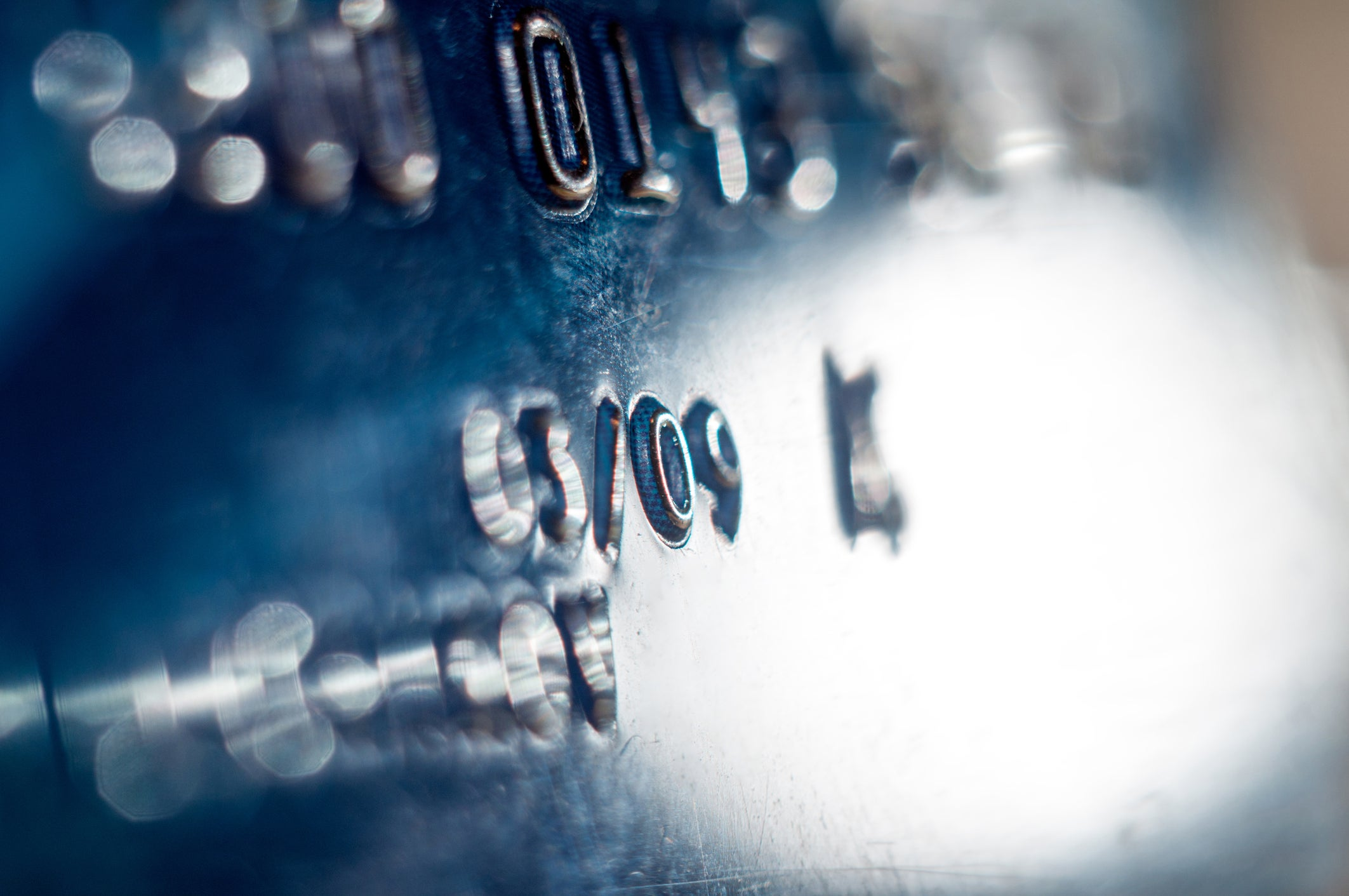 Close-up of partial credit card number on dark blue credit card.