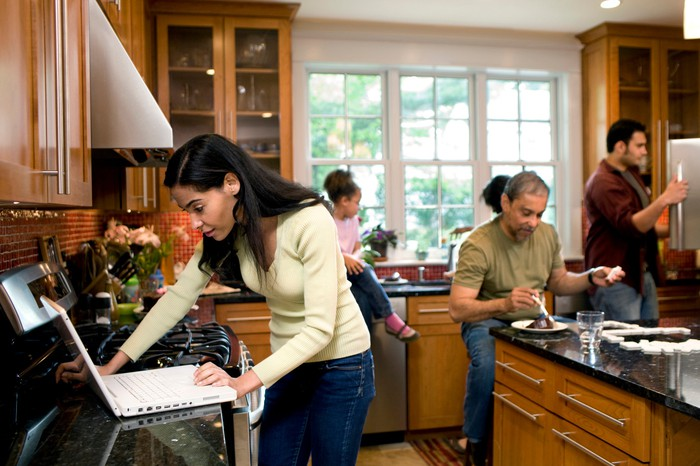 Multiple generations are seen in a kitchen.